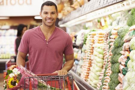Man Pousser Trolley Par Produce Counter En Supermarché Banque d'images - 42271188