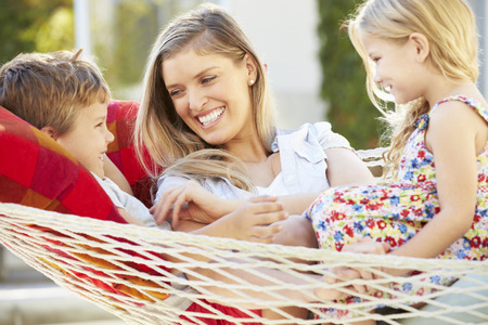 madre hijos: Mother And Children Relaxing In Garden Hammock Together