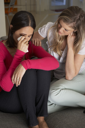 comforting: Woman Sitting On Sofa Comforting Unhappy Friend