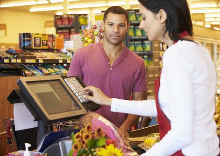 スーパー マーケットのレジで買い物を払ってお客様