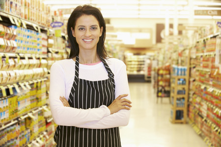 Supermarket Worker Standing In Grocery Aisle