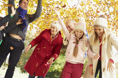 8 year old girl: Multl Generation Family Throwing Leaves In Autumn Garden