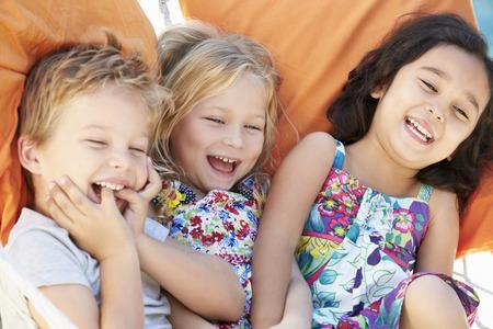 three children: Three Children Relaxing In Garden Hammock Together Stock Photo