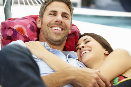 couple relaxing: Romantic Couple Relaxing In Garden Hammock Together Stock Photo