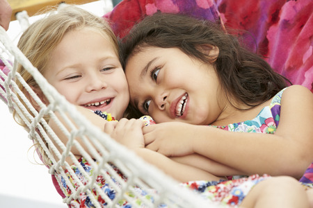 4 5 year old: Two Young Girls Relaxing In Garden Hammock Together Stock Photo