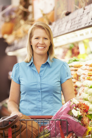 vegetable salad: Woman Pushing Trolley By Produce Counter In Supermarket Stock Photo