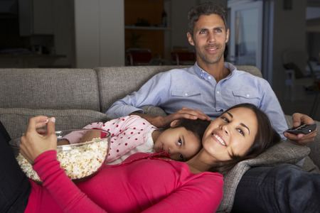 hispanic girls: Hispanic Family On Sofa Watching TV And Eating Popcorn Stock Photo