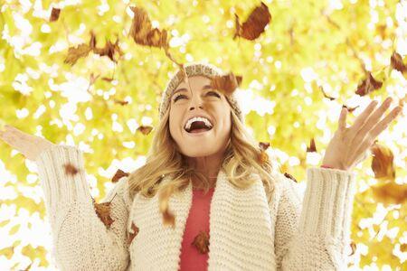 Frau wirft Autumn Leaves In The Air Standard-Bild - 42271462