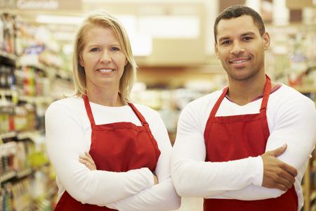 食料品店の通路で立っているスーパー マーケット労働者 写真素材