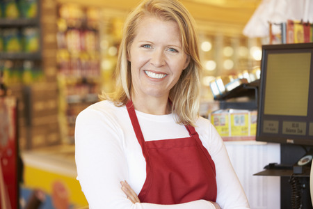 supermarket checkout: Female Cashier At Supermarket Checkout