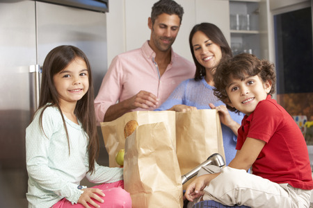 Family Unpacking Grocery Shopping In Kitchen Stock Photo