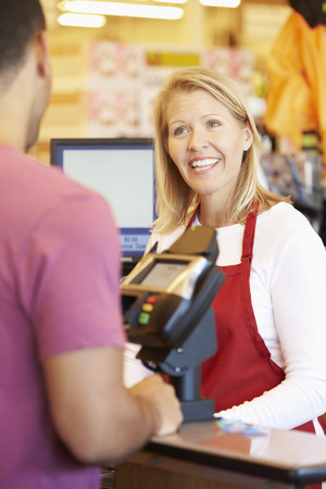 Customer Paying For Shopping At Supermarket Checkout