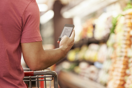 shopping trolley: Close Up Of Man Reading Shopping List From Mobile Phone In Supermarket
