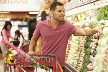 남자 슈퍼마켓에서 제작 카운터에서 트롤리를 밀어