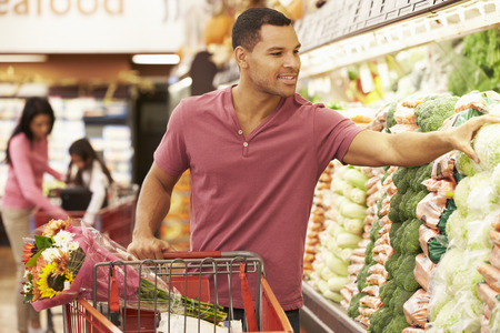 supermarket trolley: Man Pushing Trolley By Produce Counter In Supermarket