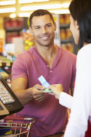 supermarket checkout: Customer Using Vouchers At Supermarket Checkout