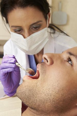 check up: Man Having Check Up At Dentists Surgery Stock Photo