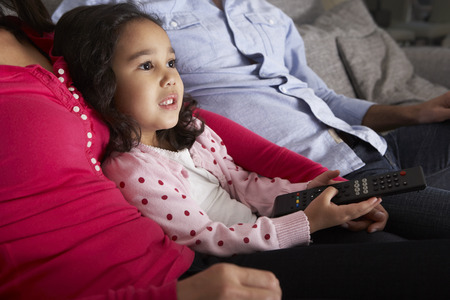 hispanic people: Hispanic Girl Sitting On Sofa And Watching TV With Parents