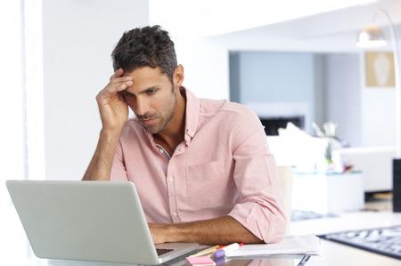 De beklemtoonde Mens die bij Laptop In Thuiskantoor Stockfoto