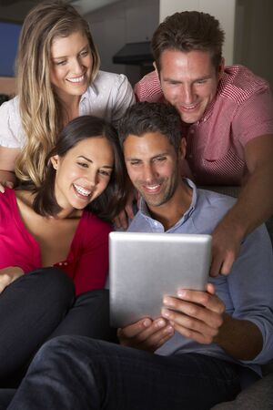 vetical: Group Of Friends Sitting On Sofa Looking At Digital Tablet