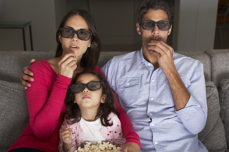 popcorn bowls: Family Watching TV Wearing 3D Glasses And Eating Popcorn Stock Photo