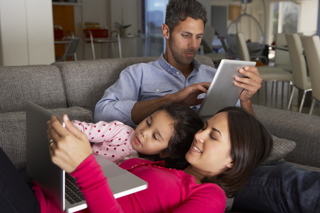 Hispanic Family On Sofa Using Laptop And Digital Tablet Banque d'images