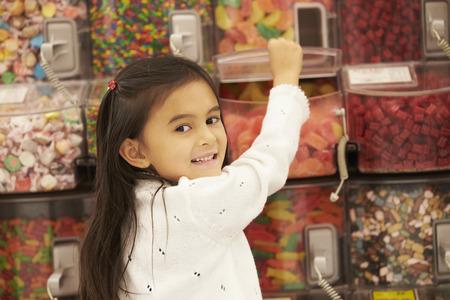 golosinas: Chica En El Contador Caramelo En Supermercado Foto de archivo