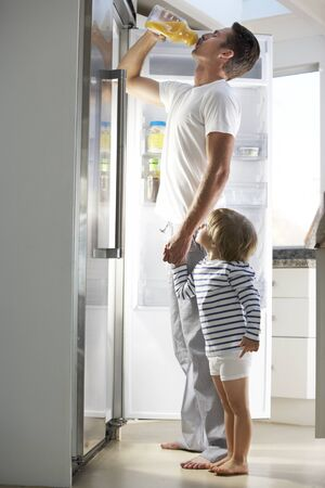 vertical fridge: Father And Son Raiding The Fridge For Drink