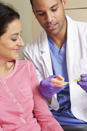 adult brushing teeth: Dentist Demonstrating How To Brush Teeth To Female Patient
