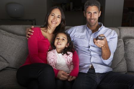 man watching tv: Hispanic Family Sitting On Sofa And Watching TV Stock Photo