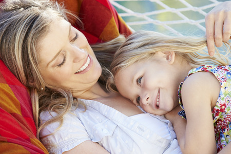 adult child: Mother And Daughter Relaxing In Garden Hammock Together Stock Photo