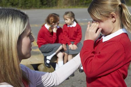 playgrounds: Teacher Comforting Victim Of Bullying In Playground