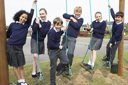 uniforms: Portrait Of Elementary School Pupils On Climbing Equipment Stock Photo