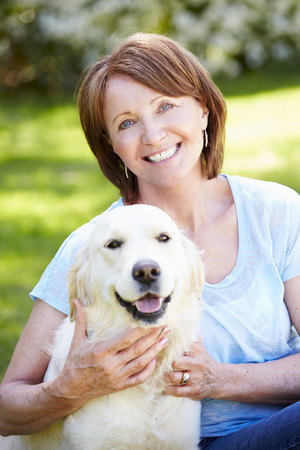 mujer con perro: Retrato de mujer madura sentado en el campo con el perro Foto de archivo