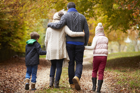 Rear View Of Family Walking Along Autumn Path Stock Photo