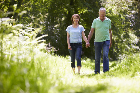 active: Senior Couple Walking In Summer Countryside