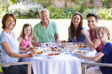 multi generation: Multi Generation Family Enjoying Outdoor Meal Together Stock Photo