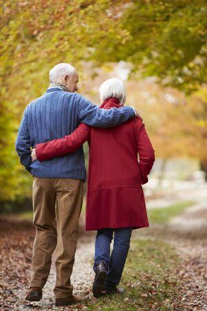 walking path: Rear View Of Senior Couple Walking Along Autumn Path
