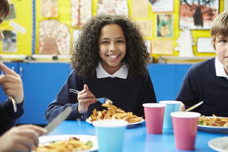 comedor escolar: Los escolares sentado en la mesa de comer el almuerzo cocinado