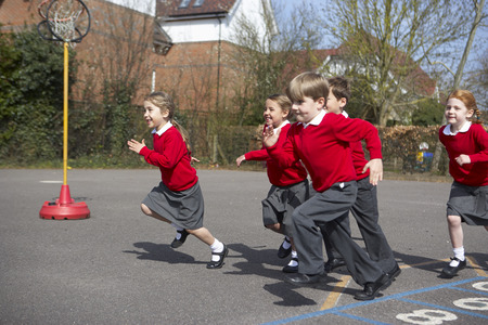 elementary: Group Of Elementary School Pupils Running In Playground