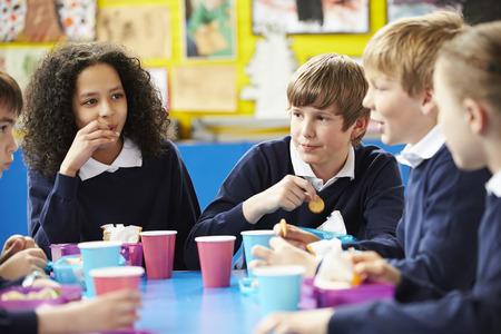 ni�o escuela: Los escolares sentado en la mesa Comer Almuerzo en lonchera