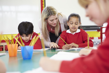 school uniforms: Teacher Helping Female Pupil With Writing Reading At Desk Stock Photo