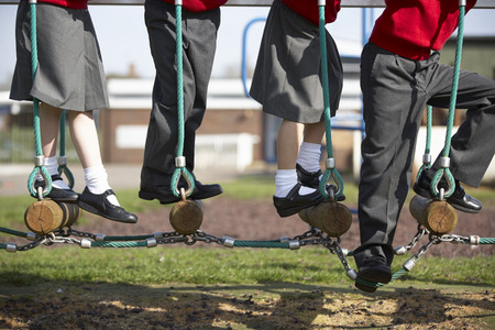 school uniforms: Close Up Of Elementary School Pupils On Climbing Equipment Stock Photo