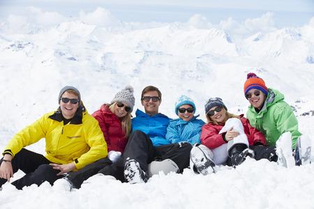 personas sentadas: Grupo de amigos que se divierten en fiesta del esquí en montañas Foto de archivo