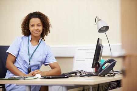 nurse computer: Portrait Of Female Nurse Working At Desk In Office Stock Photo