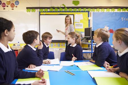 Žáci sedí u stolu jako učitel stojí Tabule Reklamní fotografie