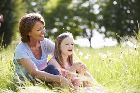 9 year old: Grandmother And Granddaughter Sitting In Summer Field