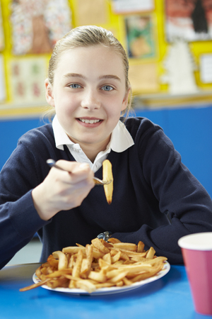 11 year old girl: Female Pupil Eating Unhealthy School Lunch Stock Photo