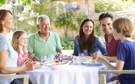 multi generation family: Multi Generation Family Enjoying Outdoor Meal Together Stock Photo