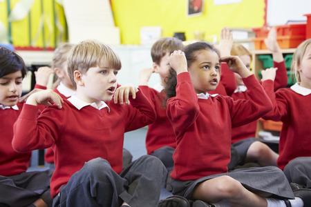ni�os estudiando: Los alumnos Perfoming acciones mientras Cantar la canci�n Foto de archivo